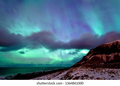 Northern lights shining at Unstad beach in Lofoten, Norway