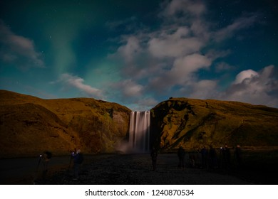 Northern lights showing above Skogafoss waterfall in iceland with a row of tourists photograping the show