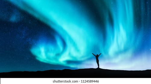 Northern lights and silhouette of standing woman with raised up arms on the hill in Norway. Aurora borealis and happy girl. Starry sky, green polar lights. Night landscape. Travel background. Concept