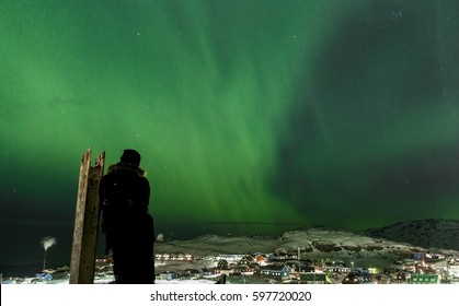 Northern lights in the sky above colorful house city in qaqortoq greenland.