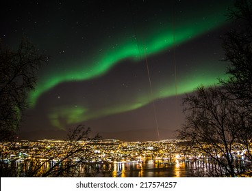 Northern lights in the sky above Tromso city in northern Norway