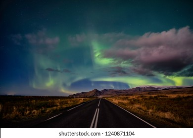 Northern lights in the sky over farming fields in southern Iceland. green band contrasting against a white cloud in the night sky