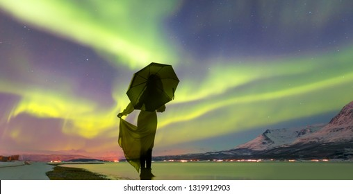 Northern lights in the sky over Tromso, Norway - Young girl in dress holding red umbrella and walking on the calm sea