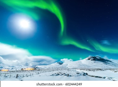Northern lights sky over winter snow mountain village. Aurora borealis