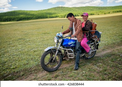 NORTHERN MONGOLIA , MONGOLIA - AUG 13, 2011: Mongol traveling with his wife on a motorcycle, stopped to talk with foreign tourists.
