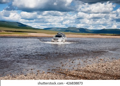 NORTHERN MONGOLIA, MONGOLIA - AUG 13, 2011: Foreign tourists in cars crossing Uur river  in northern Mongolia.