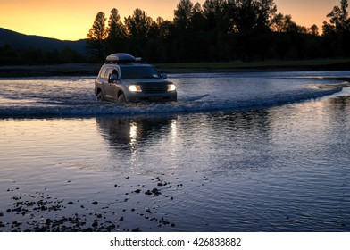 NORTHERN MONGOLIA, MONGOLIA - AUG 13, 2011: Foreign tourists in cars crossing Uur river in northern Mongolia in the evening at sunset.