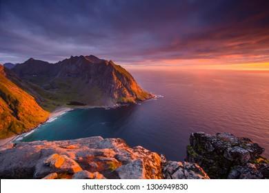 Northern Norway coastline at sunset. Rocks under red pink arctic sky. Ryten mountain on Lofoten islands.