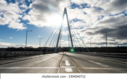 Northern Spire Bridge (opened Summer 2018) in Sunderland spanning the River Wear.  Photo taken facing the sun giving the bridge a silhouette contrasting with the blue sky with dark and white clouds.