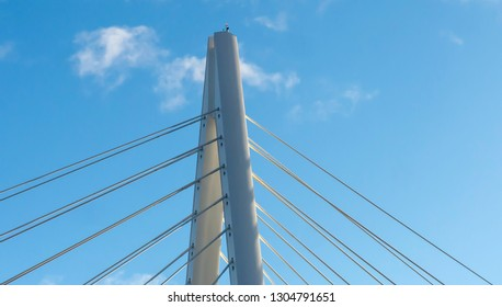 The Northern Spire Road and Pedestrian Bridge in Sunderland spanning the River Wear.  Photo taken of the top spire of the bridge showing cables and the white metal structure against the blue sky.