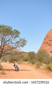 NORTHERN TERRITORY, AUSTRALIAN - OCTOBER 22: A visitor sitting close to Kata Tjuṯa a group of 36 red-rock domes of the Kata Tjuta in Tjuta National Park, Northern Territory, central Australia.