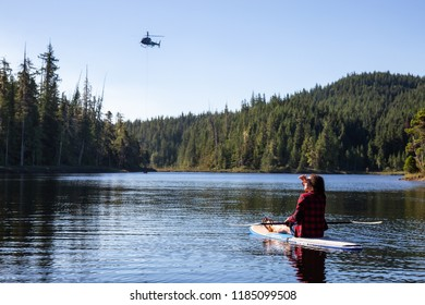 Northern Vancouver Island, British Columbia, Canada - August 17, 2018: Girl on a paddle board is watching an helicopter fighting BC Wild Forest Fires.