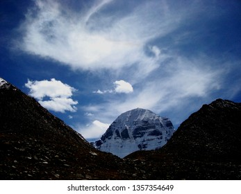 The Northern wall of Kailash in the snow, in the foreground dark rocks.