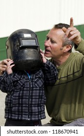 NORTHLAND - NOVEMBER 14: A New Zealander father and son looks trough a welding mask at the partial solar eclipse passes over Northland New Zealand on November 14 2012.