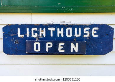 Northport, Michigan / USA 10 09 2018: Blue and white Lighthouse Open sign on White clapboard siding at Grand Traverse Lighthouse in Northport, Michigan, USA.