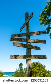 Northport, Michigan / USA 10 09 2018: Wooden sign at Grand Traverse Lighthouse on Michigan's Leelanau Peninsula pointing to Beaver Island, North Fox Island, South Fox Island, Charlevoix, and Manitou I