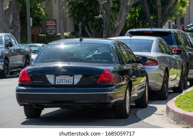 Northridge, CA / United States -  March 26, 2020: Unmarked police cars parked at the scene as LAPD Valley Homicide Detectives serve a warrant at the possible residence of a suspect.