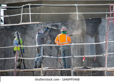 Northridge, California / USA -  February 3, 2020: A construction worker sprays concrete on a wall at a work site at 9123 Shirley Ave. Multiple workers are standing on scaffolding outside a building.