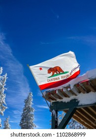 Northstar, California, USA - December 26, 2015: Northstar Ski Resort in Tahoe, A California flag ear a wooden roof. Blue sky and a tree covered with snow on the left.