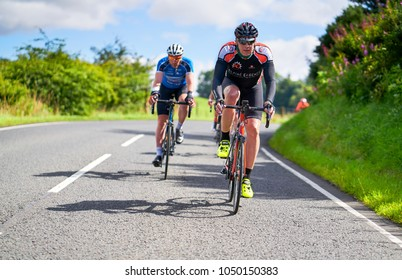 NORTHUMBERLAND, ENGLAND, UK - AUGUST 26, 2016: A group of cyclists on a bike race on country roads on a sunny day in the UK.