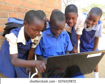 Norton, Zimbabwe,August 3 2016.  Group happy of  primary  school children in  school  uniform using  a  laptop  outside their  classroom at school.