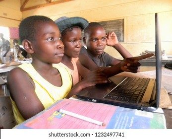 Norton,Zimbabwe,23 October 2018. Close-up of    group  of  African  schoolgirl pointing on laptop whilst   using  a  a  laptop with classmates in class.