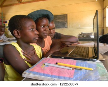 Norton,Zimbabwe,23 October 2018. A  group  of  African  schoolgirls  using  a  a  laptop  computer  to  research  and  study  whilst  in  a  classroom at school..