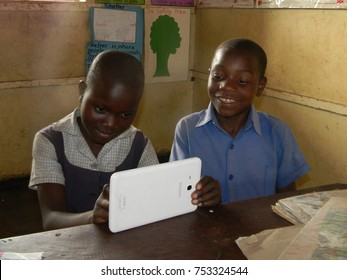 Norton,Zimbabwe,27September 2017. Two  primary  school  children  in  school uniforms  using  a  tablet whilst seated on a desk during  study  time  inside  a  classroom