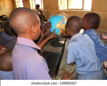Norton,Zimbabwe,October 20 2016.  Group  of primary school  children locating  countries  on  the  globe  world  map with a  laptop  beside  them in  a  classroom.