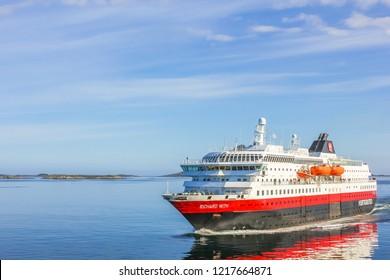 Norway, Europe - May 4, 2011: Two Hurtigruten sail in Norwegian waters. Norwegian postal boat crosses MS Richard With, in Norwegian Fjords of Lofoten Islands. Cruise ship holidays in Norwegian Coast.