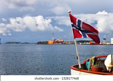 Norway flag at dramatic sky on industrial background.