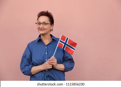 Norway flag. Woman holding Norwegian flag. Nice portrait of middle aged lady 40 50 years old with a national flag over pink wall background. Norwegian language school. Visit Norway concept.