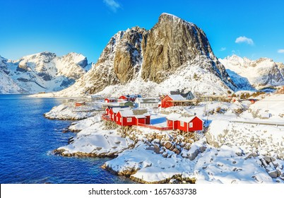 Norway, Hamnoy Scenic Viewpoint in Reine on Lofoten Islands. Red fishing houses called rorbu at Fjord bank. Amazing winter snowy landscape of Northern nature.