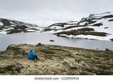 Norway, Lake Flyvotni. Near Sogn og Fjordane County Road. Norwegian Tourist Route Aurlandsfjellet runs from Aurlandsvangen to Laerdalsoyri. Traveler looks at the harsh northern nature