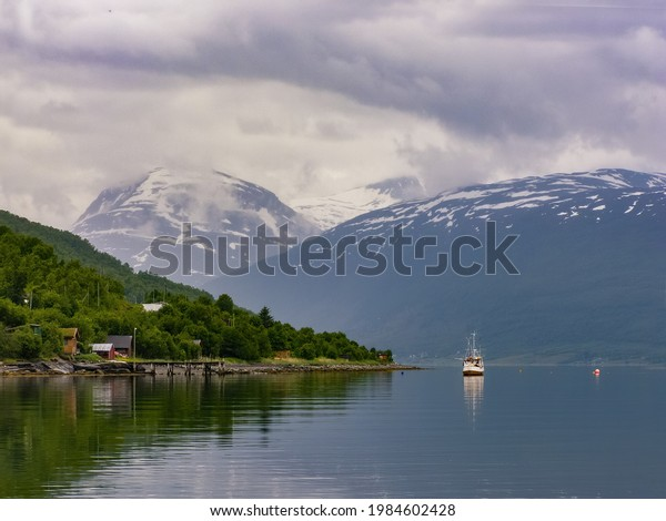 Norway landscape with a village and a ship in the middle of the fjord . Snow top mountains at background
