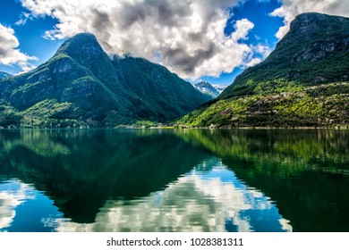 Norway landscapes. The mountains are reflecting in the water of the fjord on a sunny day