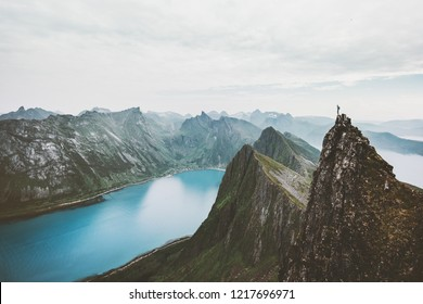 Norway mountain travel man standing on cliff edge above fjord adventure extreme climbing lifestyle journey vacations solitude emotions silence landscape