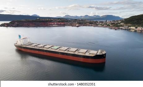 NORWAY, NARVIK - APRIL 15, 2019: Aerial shot of a iron ore cargo ship in Narvik bay, Narvik, Norway