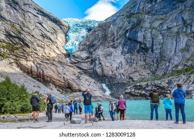 Norway, Olden - August 1, 2018: People at near lake and Briksdal or Briksdalsbreen glacier with melting blue ice, nature landmark