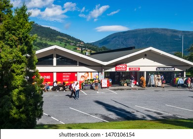 Norway, Olden - August 1, 2018: Olden town view with shops and people, mountain landscape near Nordfjord