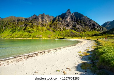 Norway. Senja island. Northern beach with white sand by the rocks. Summer norway landscape. Clear sunny day in Norway.