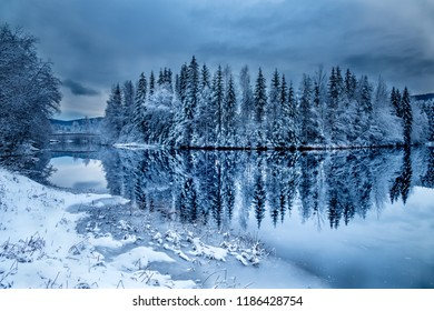 Norway, treescovered in snow reflecting prefectly in a lake
