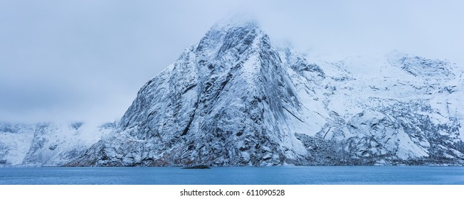 Norway winter mountain landscape, Lofoten islands. Top of mountains with snow shrouded in clouds. Panorama view