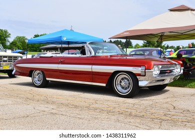 Norway, Wisconsin / USA - June 30, 2019:  A beautiful red with white inserts example of a 1961 Oldsmobile Starfire Convertible with the top down at the Wind Lake Car Show.