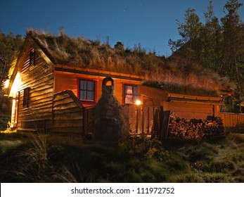 Norwegian cottage at evening enlightened by moonlight and with stars i the background