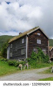 Norwegian farmhouse with a sod roof, a stone base and honing wheels in the open-air museum