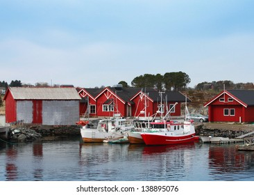 Norwegian fishing village with red wooden houses and small boats on the sea coast