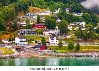 Norwegian fjord village landscape with low fog clouds, mountains and colorful houses in Olden, Norway