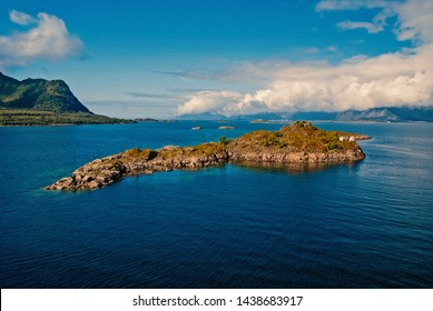 norwegian fjords. Island stony surrounded sea water in Norway. Best nature places to visit in Norway. Seascape with island on sunny day. Serenity and idyllic. Island stony cliffs coast.