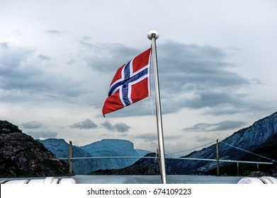 Norwegian flag in the background of the bridge and the fjord surrounded by mountains. Cloudy weather, dramatic sky of Cumulus clouds